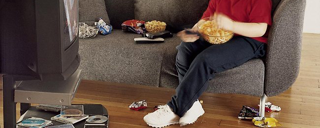 695192-overweight-child-eating-junk-food-on-couch-in-front-of-tv